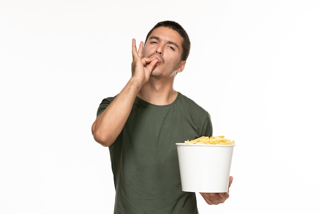 Jovem homem de camiseta verde segurando uma cesta com batata cips na parede branca filme de prazer solitário de frente