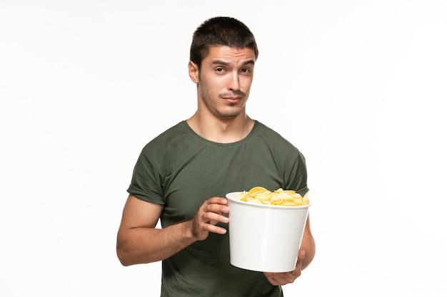 Jovem homem de camiseta verde segurando uma cesta com batata cips na parede branca filme solitário filme de prazer