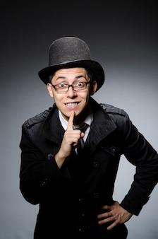 Jovem homem de casaco preto e chapéu contra cinza
