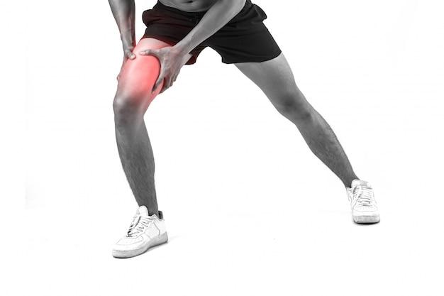 Jovem homem de esporte com fortes pernas atléticas com joelho com as mãos doloridas depois de sofrer lesão do ligamento isolado no branco.