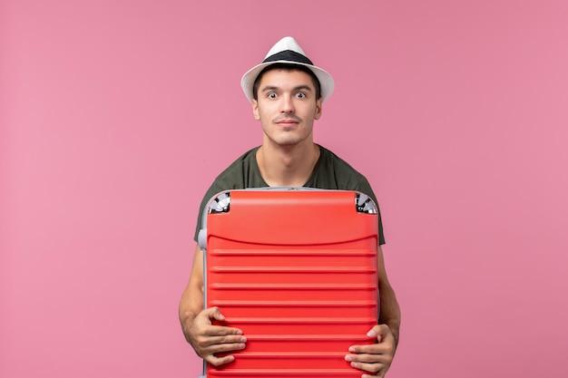 Jovem homem de férias de frente com bolsa vermelha no espaço rosa