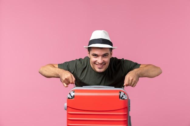 Jovem homem de férias de frente com bolsa vermelha sorrindo no espaço rosa