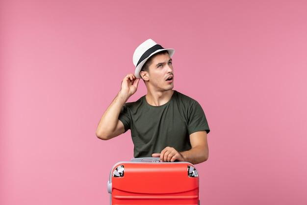 Jovem homem de férias de frente com sua bolsa vermelha na mesa rosa