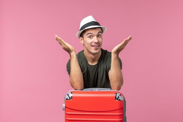 Jovem homem de férias de frente com sua bolsa vermelha no espaço rosa