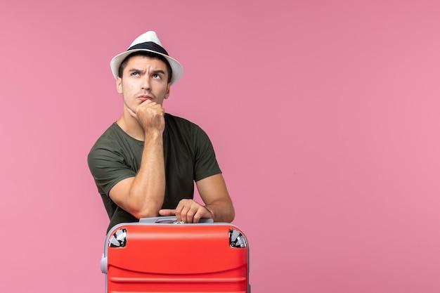 Jovem homem de férias de frente com sua bolsa vermelha pensando no espaço rosa
