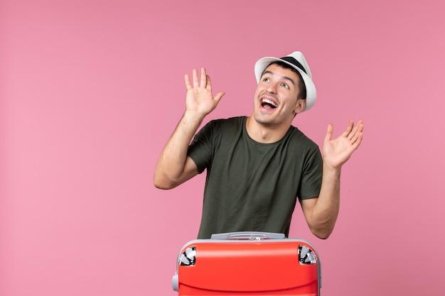 Jovem homem de férias de frente se sentindo animado com o espaço rosa