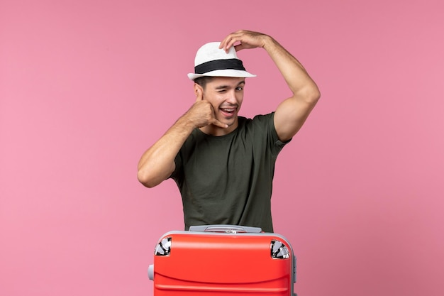 Jovem homem de férias usando chapéu na mesa rosa