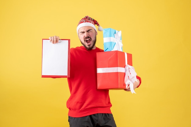 Jovem homem de frente com o presente de natal e uma nota sobre fundo amarelo