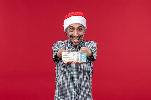 Jovem homem de frente feliz segurando o bilhete sobre fundo vermelho