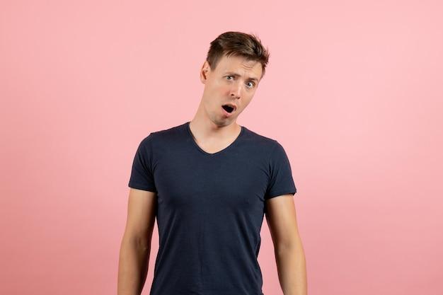 Jovem homem de frente para uma camiseta escura com uma expressão de surpresa no fundo rosa