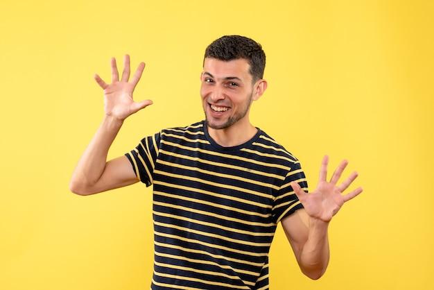 Jovem homem de frente para uma camiseta listrada em preto e branco abrindo as mãos em um fundo amarelo isolado