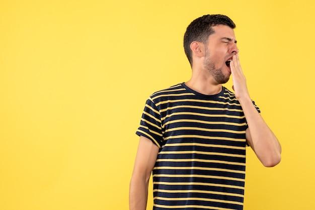 Jovem homem de frente para uma camiseta listrada em preto e branco bocejando em um fundo amarelo