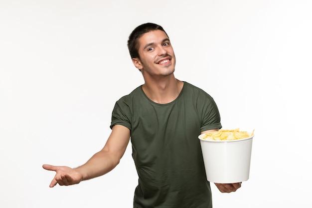 Jovem homem de frente para uma camiseta verde com batata cips e um sorriso na parede branca filme solitário pessoa cinema