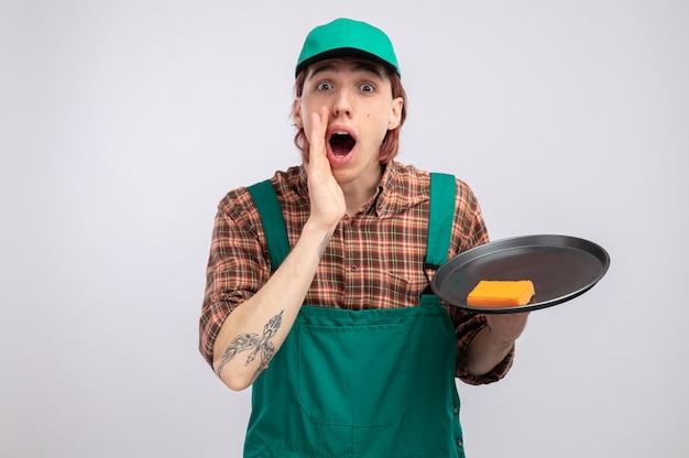 Jovem homem de limpeza com macacão de camisa xadrez e boné segurando a bandeja e a esponja, contando fofocas, segurando a mão perto da boca, em pé sobre uma parede branca