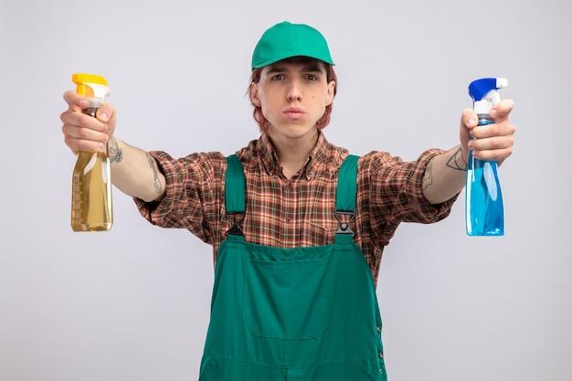 Jovem homem de limpeza com macacão e boné de camisa xadrez segurando frascos de spray de limpeza com cara séria, pronto para limpar, em pé sobre uma parede branca
