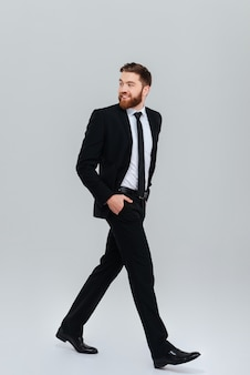 Jovem homem de negócios barbudo de terno preto se move com as mãos nos bolsos no estúdio e olhando para trás vista lateral fundo cinza isolado