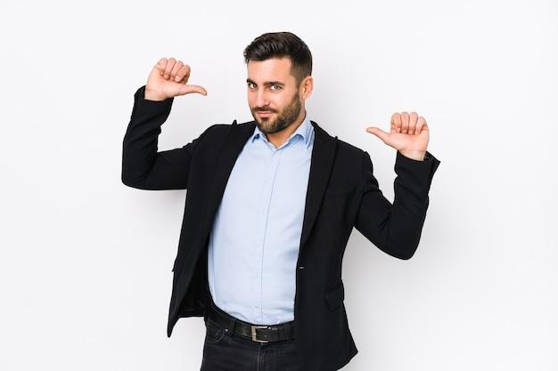Jovem homem de negócios caucasiano contra um espaço em branco isolado sente-se orgulhoso e autoconfiante, exemplo a seguir.