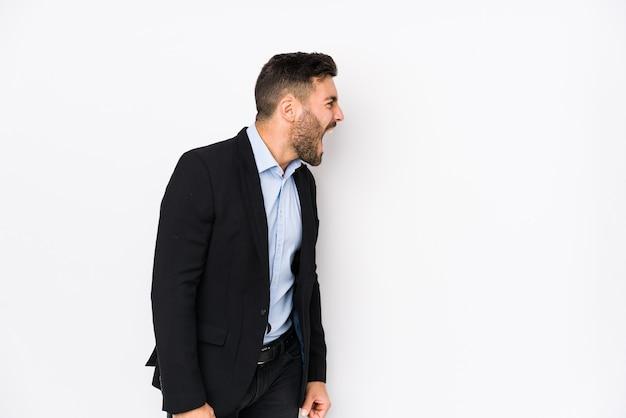 Jovem homem de negócios caucasiano contra um fundo branco isolado gritando por um espaço de cópia