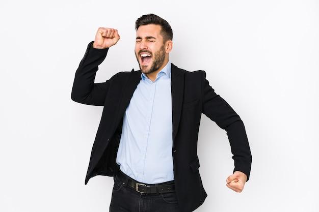 Jovem homem de negócios caucasiano em fundo branco isolado, comemorando um dia especial, pula e levanta os braços com energia.