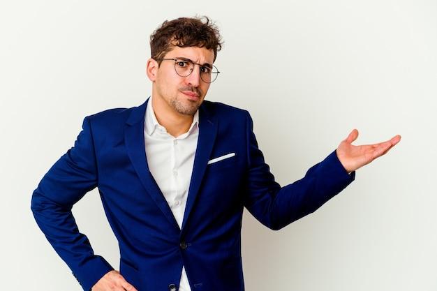 Jovem homem de negócios, caucasiano, isolado na parede branca, duvidando e dando de ombros em um gesto de questionamento