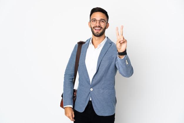 Jovem homem de negócios caucasiano isolado na parede branca sorrindo e mostrando sinal de vitória