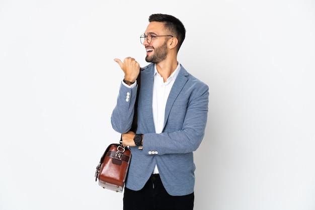 Jovem homem de negócios caucasiano isolado no fundo branco apontando para o lado para apresentar um produto