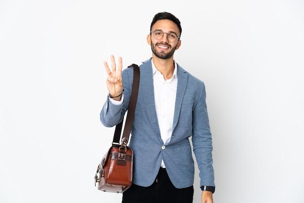 Jovem homem de negócios caucasiano isolado no fundo branco feliz e contando três com os dedos