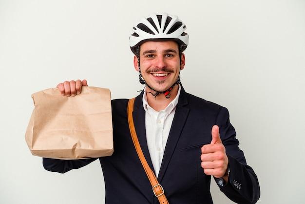 Jovem homem de negócios caucasiano usando capacete de bicicleta e segurando comida levar comida isolada no fundo branco, sorrindo e levantando o polegar