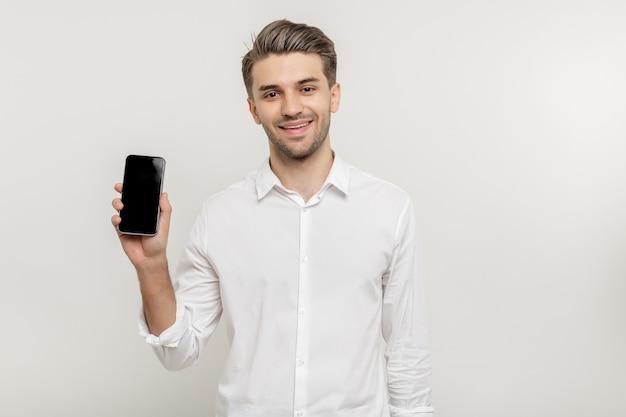 Jovem homem de negócios de camisa branca segurando um smartphone de tela em branco isolado no fundo branco