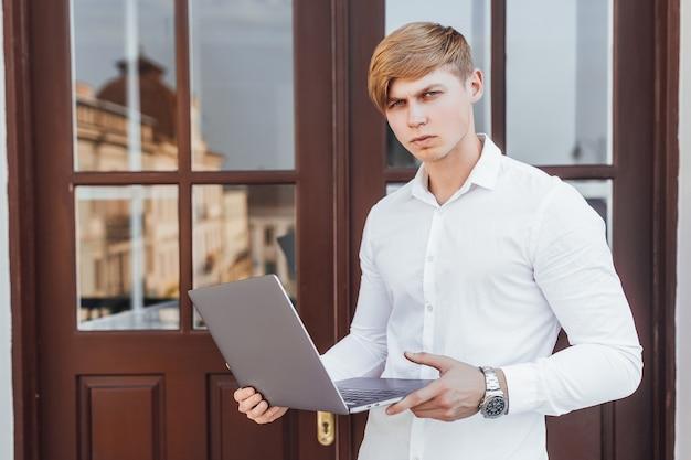 Jovem homem de negócios de sucesso em estilo empresarial com o laptop nas mãos