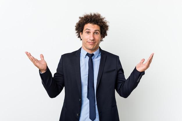 Jovem homem de negócios encaracolado contra uma parede branca duvidando e dando de ombros em um gesto questionador