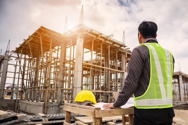 Jovem homem de negócios, engenheiro profissional, trabalhador na construção de uma casa com planta.