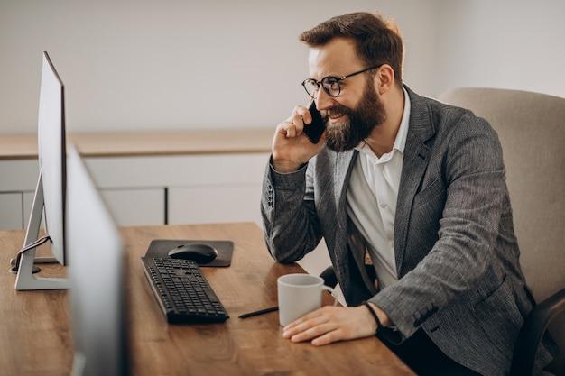 Jovem homem de negócios falando ao telefone e trabalhando no computador
