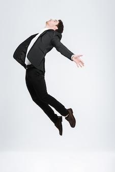 Jovem homem de negócios feliz de terno preto voando isolado em uma parede branca