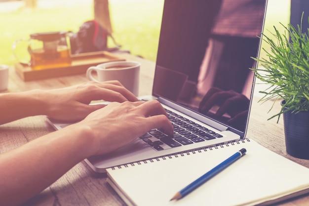 Jovem homem de negócios mão segurando copo café e usando computador portátil na cafeteria com vintage tonificado.
