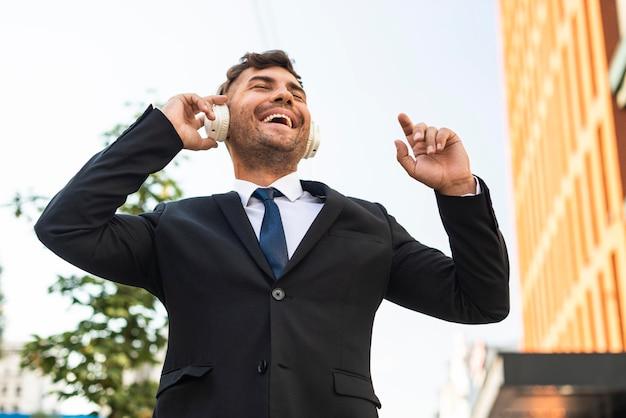 Jovem homem de negócios ouvindo música em baixa visão