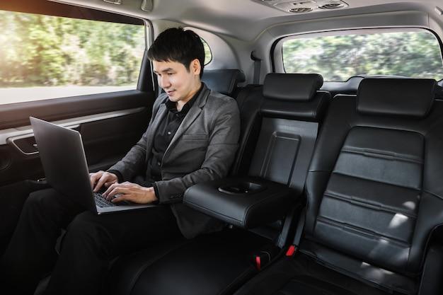 Jovem homem de negócios usando um laptop enquanto está sentado no banco de trás do carro