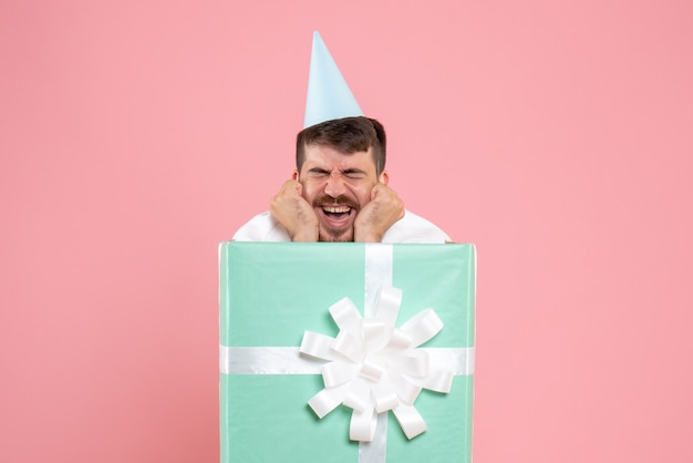 Jovem homem de pé dentro da caixa de presente na cor rosa claro foto emoção festa do pijama