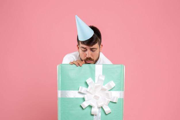 Jovem homem de pé dentro da caixa de presente na foto rosa emoção humana de frente para festa do pijama de natal