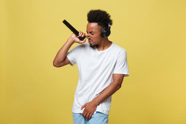 Jovem homem de pele escura com cabelo afro na camiseta branca, gesticulando com as mãos