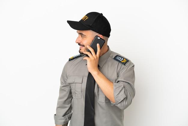 Jovem homem de segurança, caucasiano, isolado no fundo branco, conversando com alguém ao telefone celular.