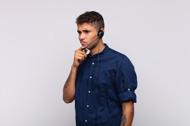 Jovem homem de telemarketing pensando, se sentindo em dúvida e confuso, com opções diferentes, imaginando qual decisão tomar