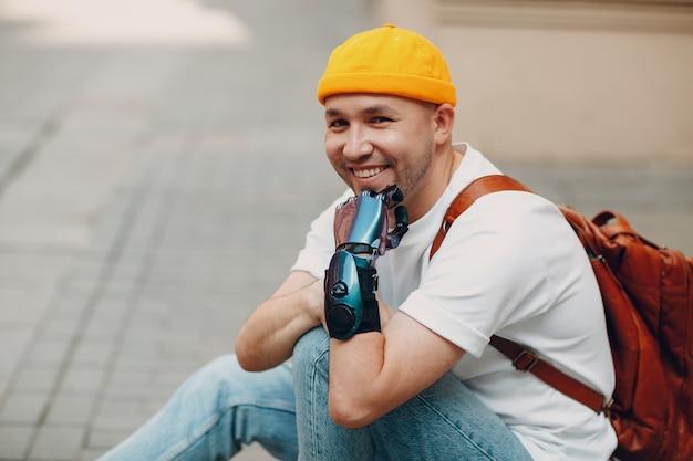 Jovem homem deficiente com prótese artificial de mão sentado na calçada da cidade ao ar livre e smili ...