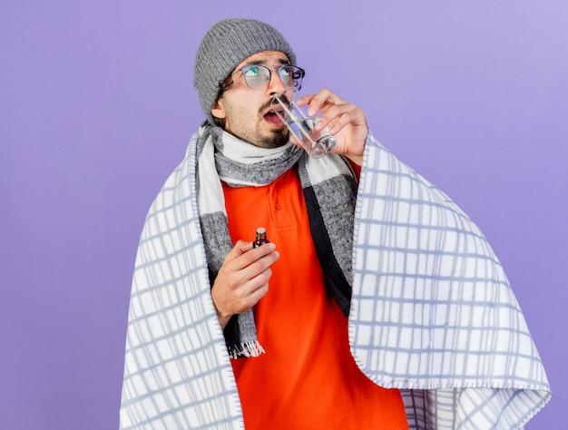 Jovem homem doente, caucasiano, usando óculos, chapéu de inverno e lenço embrulhado em xadrez segurando medicamento em um copo, olhando para cima, bebendo um copo de água isolado no fundo roxo