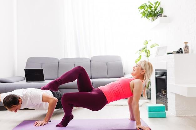 Jovem homem e mulher mulher fazendo exercício na sala ensolarada