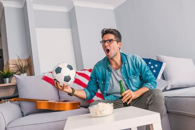 Jovem homem em casa sozinho assistindo futebol