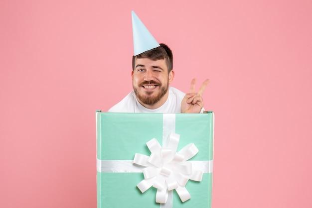 Jovem homem em pé dentro de uma caixa de presente na foto cor de rosa festa do pijama.