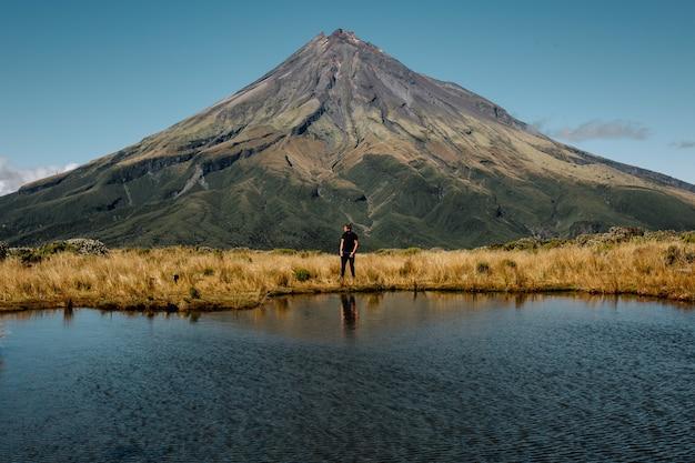Jovem homem em pé perto da alta montanha e de um lago, parque nacional de egmont norte da nova zelândia