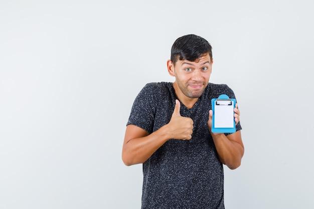 Jovem homem em t-shirt preta aparecendo baque enquanto segura seu pequeno caderno e parece feliz, vista frontal.