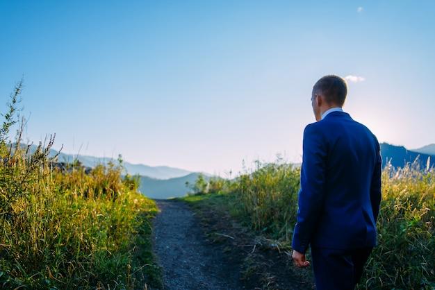 Jovem homem em um terno de negócio no fundo das montanhas vai ao seu objetivo em um dia ensolarado de verão